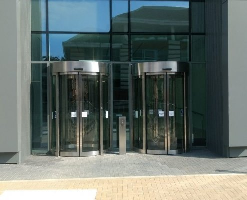 A pair of EA Curved Sliding Doors installed within a glass wall